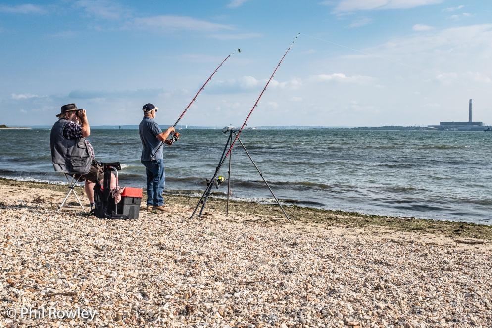 Fisherman fishing from shore on Southampton Water, UK